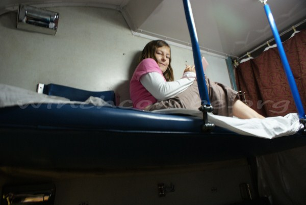 Amy's favourite position on the train, up on the bunk with her DS
